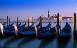 Venedig solnedgång med suddiga gondoler Fantastisk blått- och lilahimmel Arkivbilder