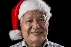 Venerable Man with Red Father Christmas Cap. Aged gentleman, wearing a red and white Old Father Christmas hat, is smiling. Bright teeth are showing. Black Stock Images