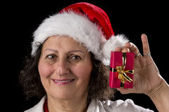 Venerable Woman with Red Cap Holding Small Gift. Smiling mature woman with a red Father Christmas cap is holding up her left hand and offering a small wrapped Stock Photo