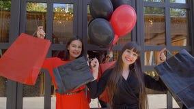 Venerdì nero, le amiche alla moda si rallegrano il nuovo acquisto dal boutique nella vendita stagionale stock footage