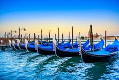 Venetië, gondels of gondole op zonsondergang en kerk op achtergrond. Italië Stock Foto's