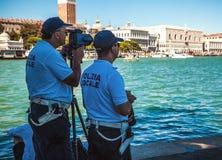 VENETIË, ITALIË - AUGUSTUS 17, 2016: De politiemannen letten op toeristen door speciaal optisch materiaal op 17 Augustus, 2016 in Royalty-vrije Stock Afbeeldingen