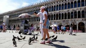 Venetië, Italië - Juli 7, 2018: de mening van gelukkig mens en jong geitjemeisje, toeristen, die duiven houden, die speelt met he stock video