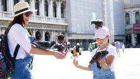 Venetië, Italië - Juli 7, 2018: de mening van gelukkig vrouw en jong geitjemeisje, toeristen, die duiven houden, die speelt met h stock videobeelden