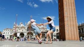 Venetië, Italië - Juli 7, 2018: mening van gelukkig mooi vrouw en jong geitjemeisje, toeristen, die handen houden, die op Piazza  stock video