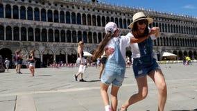 Venetië, Italië - Juli 7, 2018: mening van gelukkig mooi vrouw en jong geitjemeisje, toeristen, die handen houden, die op Piazza  stock videobeelden