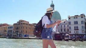 VENETIË, ITALIË - JULI 7, 2018: toeristenvrouw in hoed, borrels, een rugzak op haar schouders, die in haar handen een kaart houde stock footage