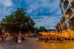VENETIË, ITALIË - JUNI 18, 2015: Grote bomen in het midden van aardig vierkant in Venetië, mensen die en bij pizzeria lopen eten Stock Foto's