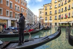 Venetië, Italië - November 27, 2018: Orseolobassin Bacino Orseolo in Venetië Venetiaanse gondelier die gondel wegschoppen door gr stock foto's