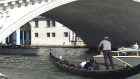 Venetië, Italië September 2018 De gondel met toeristen zwemt onder de Rialto-brug stock footage