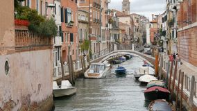 VENETIË, ITALIË, 7 SEPTEMBER, 2017: Een comfortabel mooi Venetiaans kanaal met een brug en mooie kleurrijke huizen stock footage