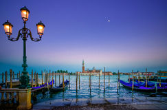 Venetië, straatlantaarn en gondels of gondole op zonsondergang en kerk op achtergrond. Italië Stock Fotografie