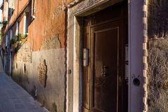 Venetian ally with wooden door, leading to a courtyard. Focus on details of Venetian artistry on display throughout the city streets and canals, including Stock Photo