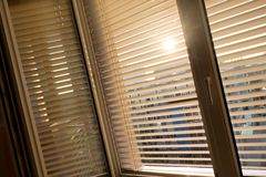 Venetian blinds for shade at the window. To protect against heat and sun blinds are attached to a window Royalty Free Stock Image