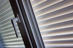 Venetian blinds for shade at the window. To protect against heat and sun blinds are attached to a window Stock Photo