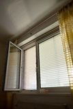 Venetian blinds for shade at the window. To protect against heat and sun blinds are attached to a window Royalty Free Stock Photos