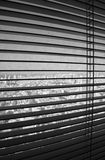 Venetian Blinds TLV. Venetian blinds in their open position, revealing a dirty window with defocused Tel-Aviv buildings and the Mediterranean sea in the Royalty Free Stock Photos