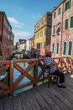 Venetian boat driver is sitting on the bridge Royalty Free Stock Images