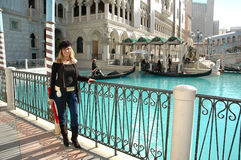 Venetian Canal. Venetian woman standing by the water canal waiting to meet someone. Woman watching lovers take rides in gondola boats Stock Photos