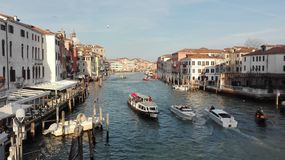 Venetian canal with gondole and boats in Venice, Italy Royalty Free Stock Images
