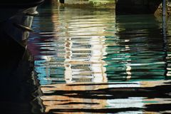 Venetian canal. A narrow canal with blue, green and orange colors reflecting the shapes of a bridge, in Venice, in Italy, Europe royalty free stock photos