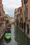 Venetian canal and promenade. Dramatic Venetian cityscape. Canal and promenade Stock Images