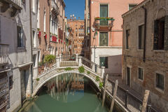 Venetian canal. Stone bridge over one of the smaller canals in the back waterways of Venice stock image