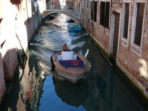 Venetian canal. Woman with a beautiful boat passing through Venice Stock Image