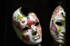 Venetian carnival art mask, for women. White color with drawings of small flowers. Uniform black background. Copy space royalty free stock photography