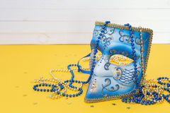 Venetian carnival blue mask with beads on a yellow background. Stock Photography