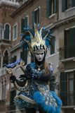 Venice Carnival character dressed in a colourful blue and yellow costume and venetian mask with a harp Venice Italy stock photo