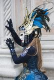 Venice Carnival character dressed in a colourful blue and gold costume and Venice mask at February Venice Italy. Venice Carnival character dressed in a colourful royalty free stock images