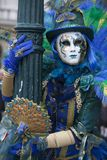 Venice Carnival character dressed in a colorful green, yellow and blue costume and venetian mask Venice Italy. Venice Carnival character dressed in a colourful royalty free stock photo