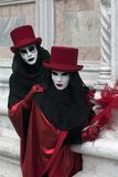2 Venetian Carnival Figures in a colorful costumes and masks under Venice Italy. 2 Venetian Carnival Figures in a colorful red and black costumes and masks Stock Photos