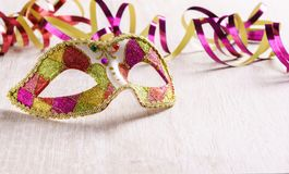 Venetian carnival mask with paper streamer on bright wood background Stock Photos