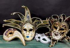 Venetian carnival masks on green wooden surface against dark background Royalty Free Stock Image