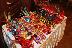 Venetian carnival masks. Party masks on a table. A group of venetian, mardi gras mask or disguise on a dark background. Mardi Gras Masks with beads. Carnaval Royalty Free Stock Image