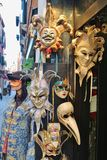 Venetian carnival masks, Venice, Italy. Venice, Italy - April 4, 2017:  Artful venetian carnival masks and historical costume at the entrance of a  handicraft Stock Images