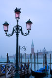 Venetian cityscape. Street lamp and gondolas with view of San Giorgio Maggiore Stock Images