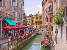 Venetian cityscape. People seat at an open air restaurant in a quiet corner of Venice near a canal , enjoying the fine spring weather Stock Photo