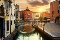 Venetian cityscape at sunrise. Venetian cityscape with water canal and small bridge at sunrise, Italy Stock Image