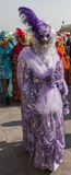 Venetian Costume. Venice,Italy- February 18, 2012: Person wearing a beautiful purple Venetian costume and mask during the Venice Carnival days Stock Images