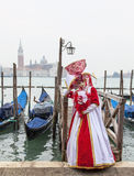Venetian Costume. Venice, Italy- February 18th, 2012: Image of a person in a beautiful red and white costume, posing in San Marco Square  in Venice during the Stock Image