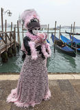 Venetian Costume with a Rose. Venice, Italy- February 19th, 2012:Image of a person in a traditional costume and mask posing with a rose near the gondolas dock in Stock Photo
