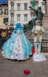 Venetian Costumes. Venice,Italy,February 26th 2011: A couple disguised in specific sophisticated Venetian costumes poses for tourists on Sestiere Castello during Stock Image