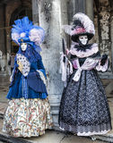 Venetian Costumes. Venice, Italy-February 18,2012: Two persons wearing specific costumes and masks in Venice during The Carnival days Royalty Free Stock Photography