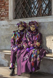 Venetian Costumes. Venice, Italy- February 18th, 2012: Two people disguised in purple Venetian costumes sitting on a bench during the Venice Carnival days Stock Image