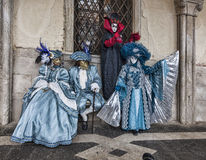 Venetian Costumes Scene. Venice, Italy- February 19th, 2012: A group of four people disguised in various Venetian costumes poses near walls of the Doge's Palace Royalty Free Stock Image