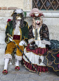 Venetian Couple. Venice, Italy- February 18th, 2012: A couple wearing traditional masks and costumes pose in San Marco Square near The Doge's Palace during The Royalty Free Stock Images