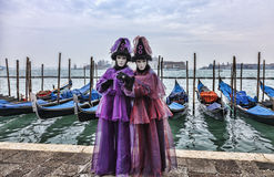 Venetian Couple. Venice, Italy- February 198th, 2012:A couple disguised in Venetian costumes pose in front of gondolas dock during the Venice Carnival days Stock Photography